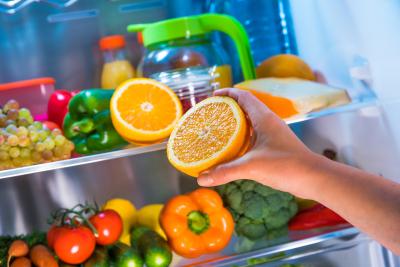 woman getting orange from the fridge